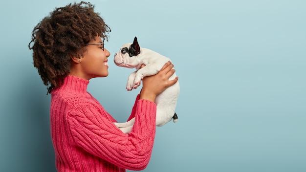 African american kobieta ubrana w różowy sweter trzyma psa