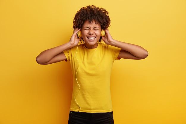 African american kobieta ubrana w żółtą koszulkę i słuchawki