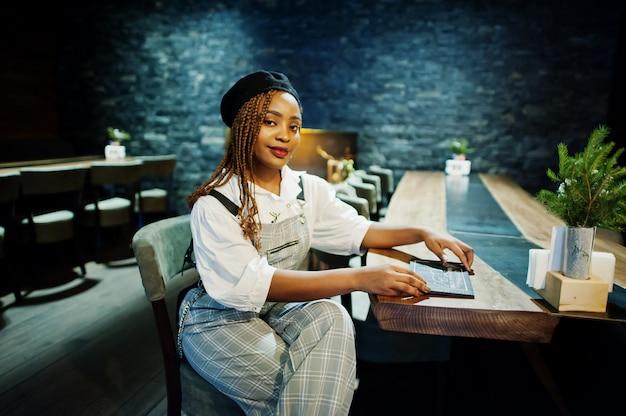 African american kobieta w kombinezon i beret w pokoju z drewnianym stołem i kominkiem.