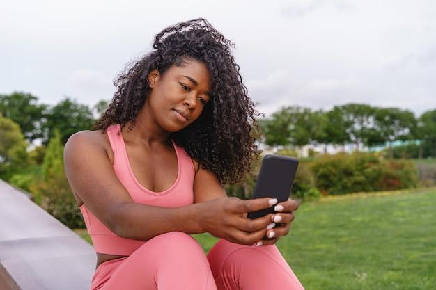 African american kobieta w sportowej za pomocą smartfona. poziomy widok kobiety fitness na zewnątrz