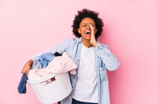 African american kobieta w średnim wieku robi pranie na białym tle krzyczy podekscytowany do przodu.