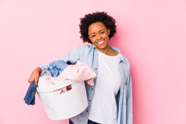 African american kobieta w średnim wieku robi pranie szczęśliwy, uśmiechnięty i wesoły.