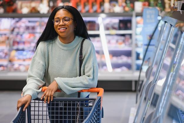 African american kobieta w supermarkecie z koszykiem.