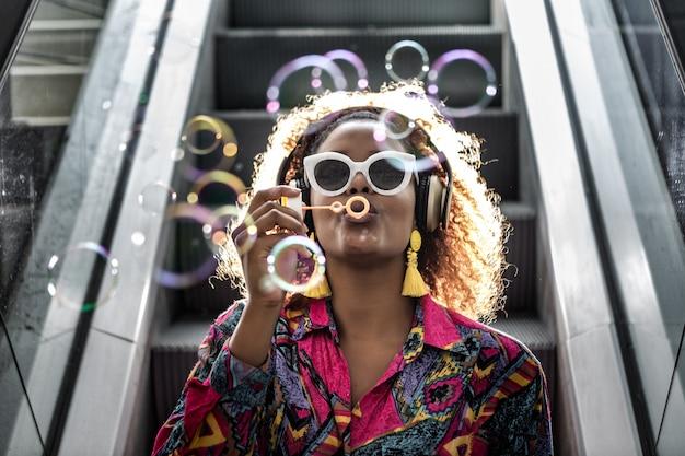 African american kobieta w zestawie słuchawkowym dmuchanie baniek na ruchomych schodach