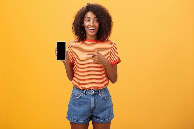 African american kobieta z kręconymi włosami, wskazując na telefon komórkowy na pomarańczowej ścianie