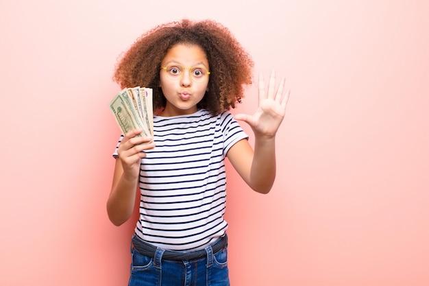 African american little girl na płaskiej ścianie z banknotów dolarowych