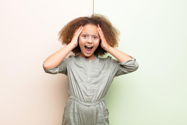 African american little girl podnosząca ręce do głowy, z otwartymi ustami, czująca się wyjątkowo szczęśliwa, zaskoczona, podekscytowana i szczęśliwa przy płaskiej ścianie