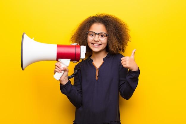 African american little girl przeciwko płaskiej ścianie trzyma megafon