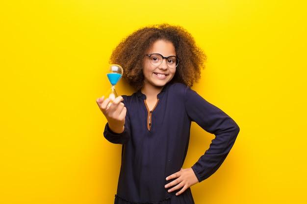 African american little girl przeciwko płaskiej ścianie trzyma zegar z piaskiem