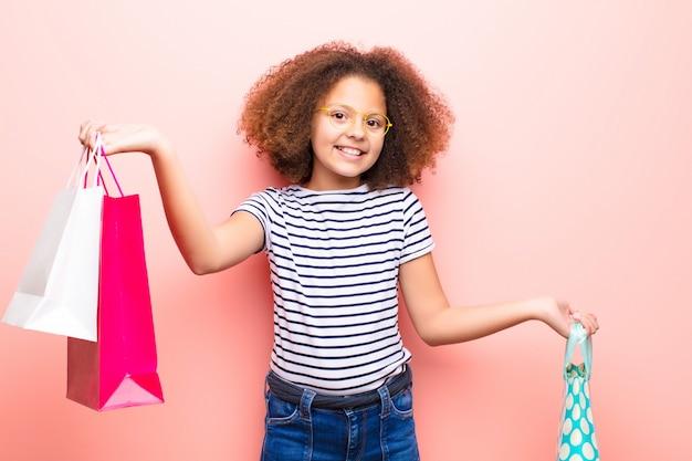 African american little girl przeciwko płaskiej ścianie z torby na zakupy