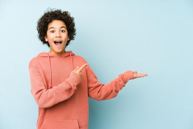African american mały chłopiec na białym tle podekscytowany, trzymając miejsce na kopię na dłoni.