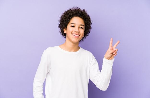 African american mały chłopiec na białym tle pokazując znak zwycięstwa i uśmiechając się szeroko.