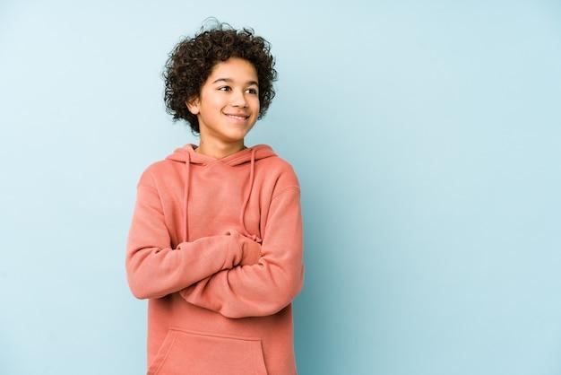 African american mały chłopiec na białym tle uśmiechnięty pewnie ze skrzyżowanymi rękami.
