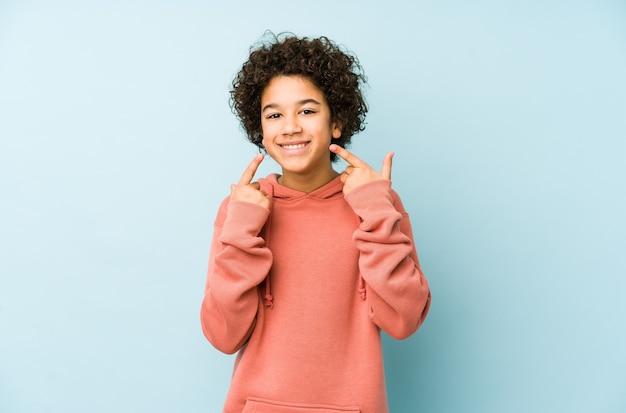 African american mały chłopiec na białym tle uśmiechy, wskazując palcami na usta.