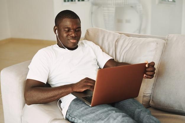African american man ogląda film na laptopie, odpoczywając na kanapie
