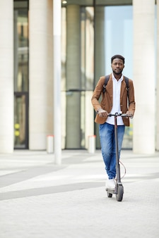 African-american man riding electric scooter