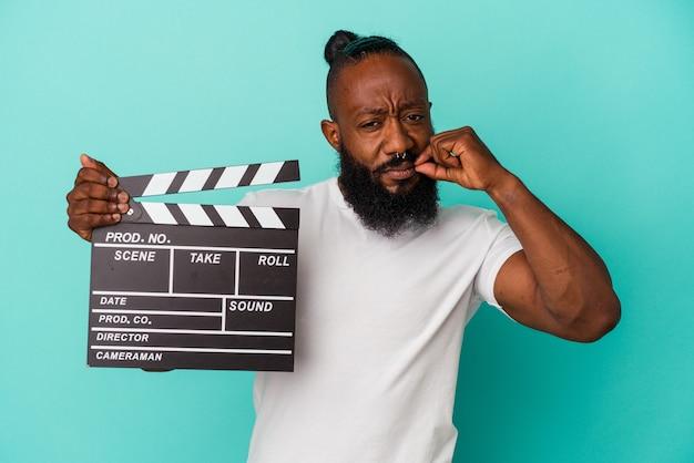 African american man trzymając clapperboard na białym tle na niebieskim tle z palcami na ustach zachowując tajemnicę.