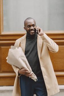 African american man w mieście. facet trzyma bukiet kwiatów. samiec w brązowym płaszczu.