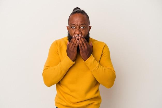 African american man z brodą na białym tle na różowe ściany obejmujące usta rękami patrząc zmartwiony.