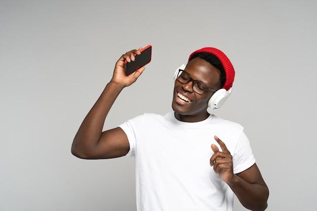 African american mężczyzna nosi czerwony kapelusz i okulary, słuchając muzyki, tańczy
