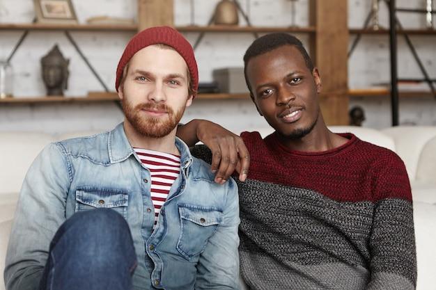 African american mężczyzna opierając łokieć na ramieniu swojego stylowego przyjaciela