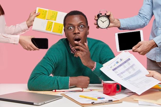 African american mężczyzna siedzi przy biurku, otoczony gadżetami i papierami