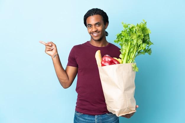 African american mężczyzna trzyma torbę na zakupy spożywcze na białym tle na niebieskim tle, wskazując palcem w bok