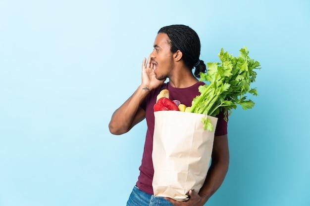 African american mężczyzna trzyma torbę na zakupy spożywcze na niebiesko, krzycząc z szeroko otwartymi ustami na bok