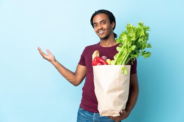 African american mężczyzna trzyma torbę na zakupy spożywcze na niebiesko wyciągając ręce na bok za zaproszenie do przyjścia
