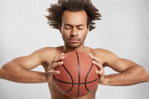 African american mężczyzna zamyka oczy, stara się skoncentrować, jak trzyma piłkę do koszykówki