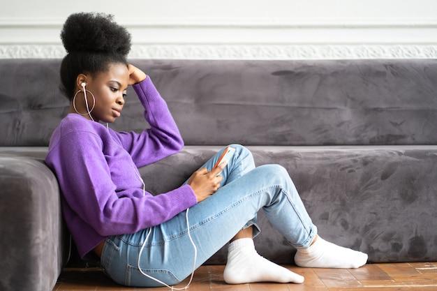 African american młoda kobieta w fioletowym swetrze siedzi na podłodze przy użyciu smartfona