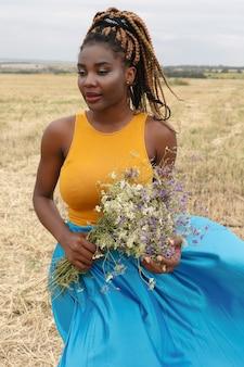 African american młoda kobieta zabawy na świeżym powietrzu o zachodzie słońca. roześmiana dziewczyna na polu. bukiet dzikich kwiatów. piękna młoda afroamerykanka z warkoczykami