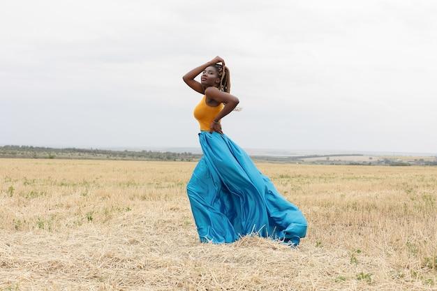 African american młoda kobieta zabawy na świeżym powietrzu o zachodzie słońca. roześmiana dziewczyna na polu. piękna młoda afroamerykanka z warkoczykami