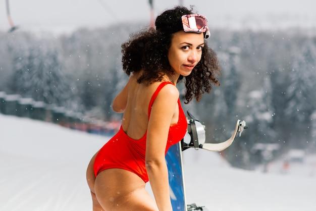 African american narciarz kobieta w stroju kąpielowym w okularach snowboardowych z radosnym wyrazem twarzy