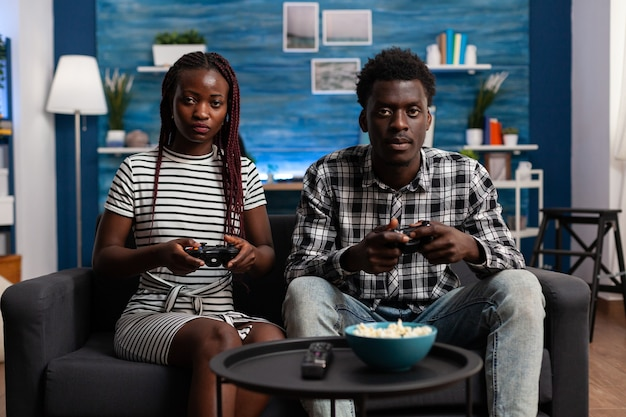 African american para grania w gry wideo na konsoli tv za pomocą joysticków na ekranie telewizora. czarni żonaci partnerzy cieszący się nowoczesną wirtualną grą dla zabawy i rozrywki w domu