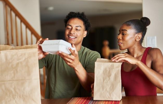 African american para siedzi przy stole patrząc na dostawę jedzenia
