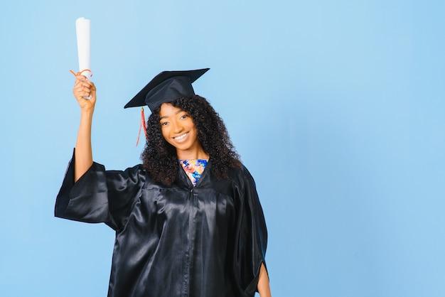 African-american piękna kobieta w czarnej szacie i kapeluszu, uśmiecha się na niebieskim tle na białym tle.