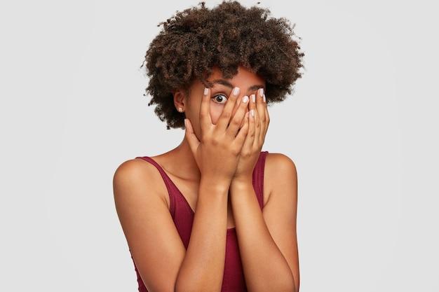 African american piękna młoda kobieta zerka przez palce, zakrywa twarz obiema rękami, ma przerażony wyraz, gdy zauważa coś strasznego lub przerażającego