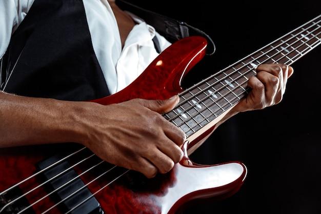 African american przystojny muzyk jazzowy gra na gitarze basowej w studio na czarnym tle. koncepcja muzyki. młody radosny atrakcyjny facet improwizacji. szczegół portret retro.