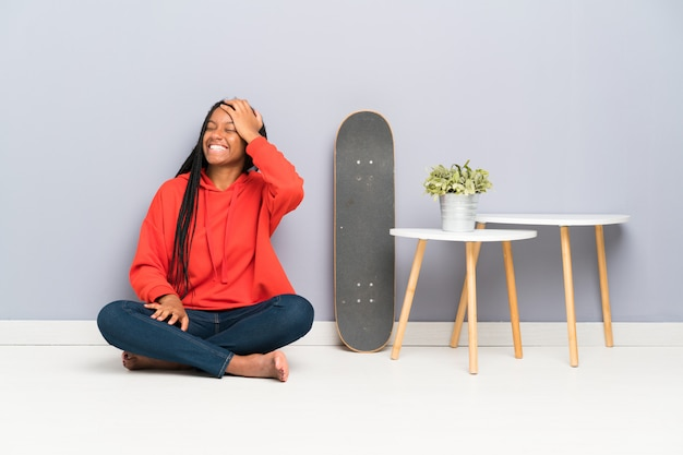 African american skater nastolatka dziewczyna z plecionymi włosami, siedząc na podłodze ze śmiechem