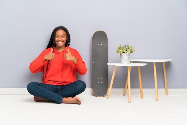 African american skater nastolatka dziewczyna z plecionymi włosami siedzi na podłodze, dając kciuki gest