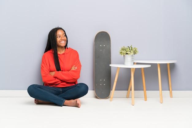 African american skater nastolatka dziewczyna z plecionymi włosami siedzi na podłodze, patrząc z boku