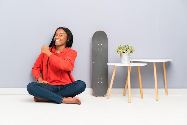 African american skater nastolatka dziewczyna z plecionymi włosami siedzi na podłodze świętuje zwycięstwo