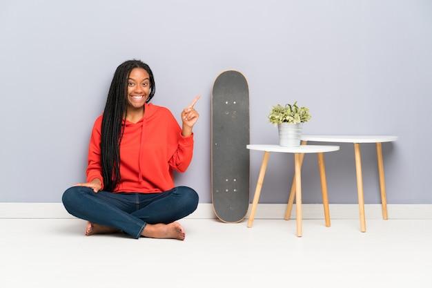 African american skater nastolatka dziewczyna z plecionymi włosami siedzi na podłodze, wskazując palcem na bok