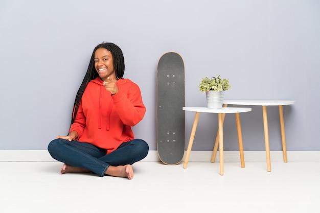 African american skater nastolatka z plecionymi włosami siedzi na podłodze wskazuje palcem na ciebie