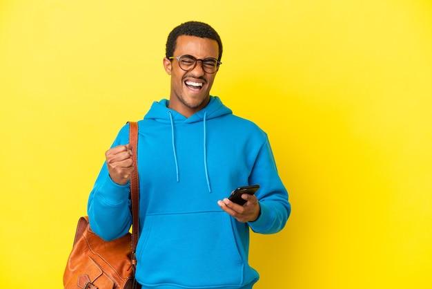 African american student mężczyzna na białym tle żółtym tle z telefonem w pozycji zwycięstwa