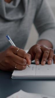 African american student pisania pracy domowej z liceum na notebooku pracującym zdalnie z domu. czarna kobieta studiująca matematykę za pomocą platformy e-learningowej podczas kursów online siedząc przy biurku
