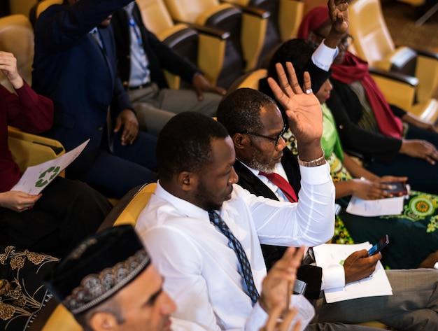 African descent man podnosi rękę na spotkanie biznesowe