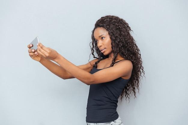 Afro american kobieta robi selfie zdjęcie na smartfonie na szarej ścianie
