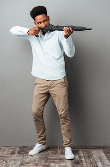 Afro amerykanin używa parasola jak pistolet i strzela